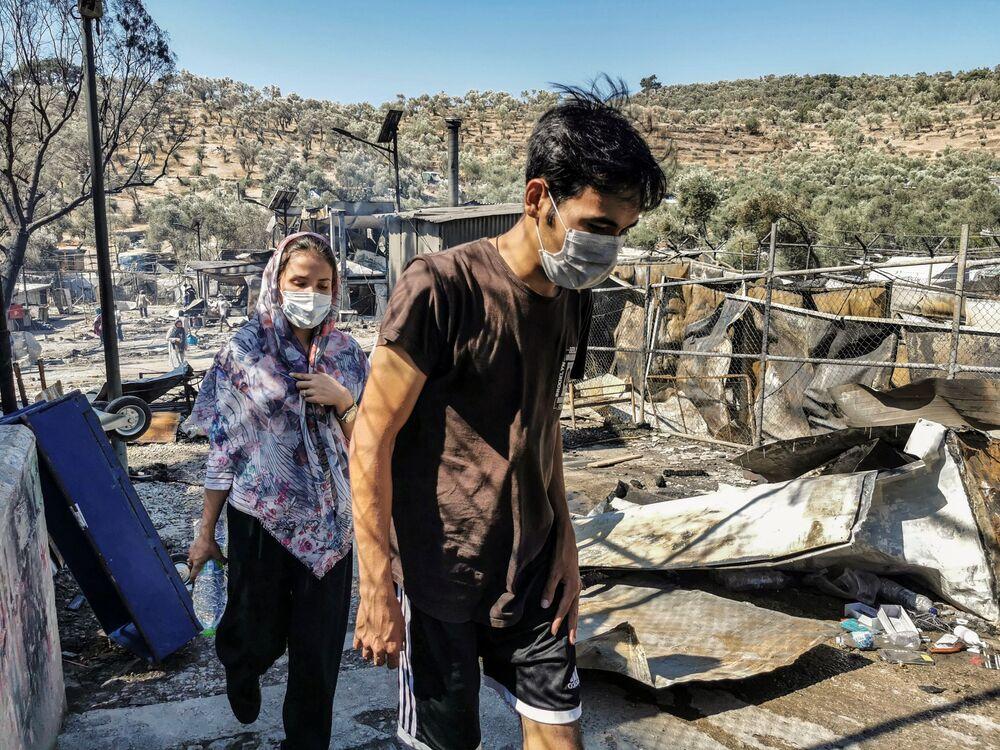 Migranci w spalonym obozie w Moria na Lesbos
