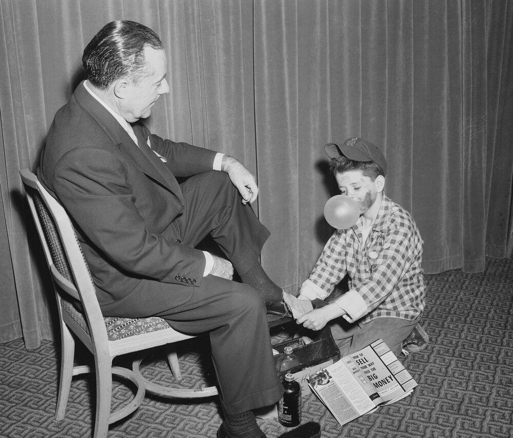 Czyściciel butów wydmuchuje balon z gumki podczas czyszczenia butów Waltera T. Shirleya, byłego komisarza ds. Handlu w Nowym Jorku, 1954 rok