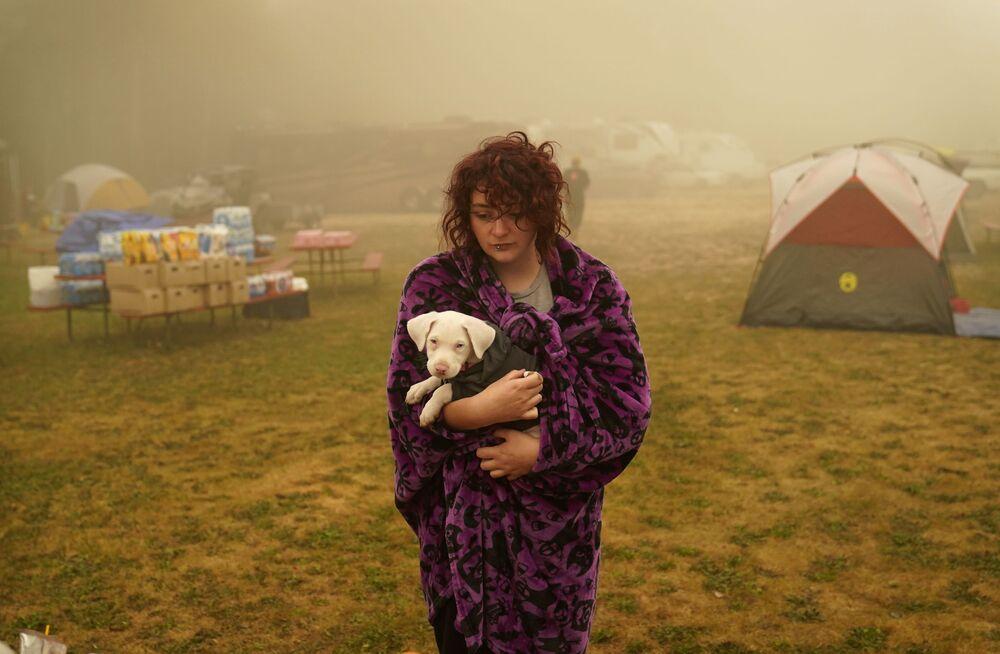 Kobieta z psem w centrum pomocy ofiarom pożarów w USA