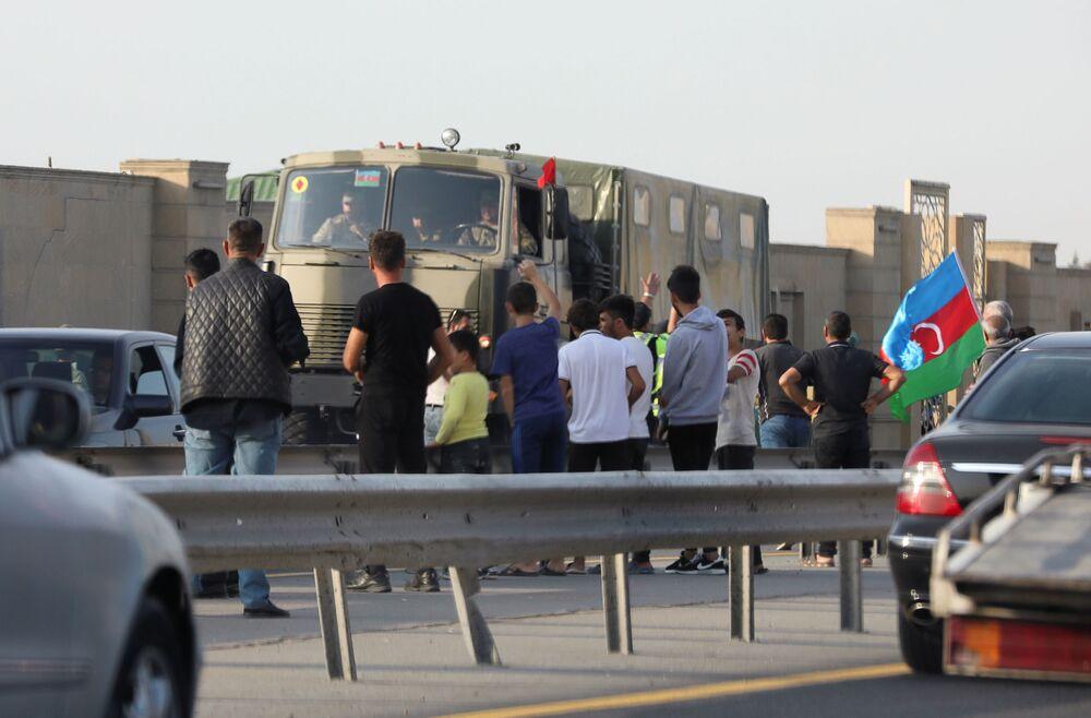 Ludzie w pobliżu ciężarówek armii azerbejdżańskiej w Baku