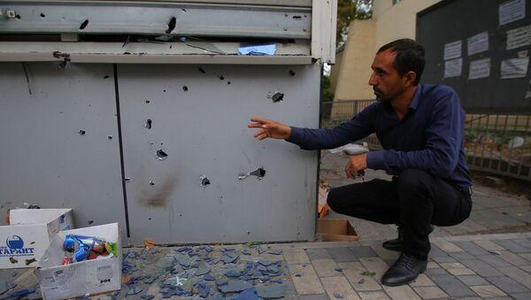 Mężczyzna podczas demonstracji skutków ostrzału w mieście Terter, Azerbejdżan - Sputnik Polska