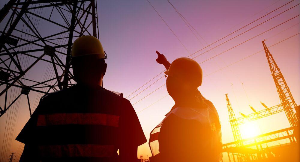 Dwóch pracowników przy wsporniku linii energetycznej