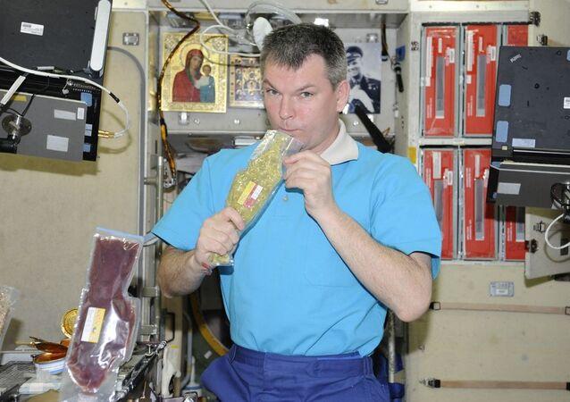 """Kosmonauta Roskosmosu Aleksandr Samokutiajew z kosmicznym jedzeniem """"Zupa ryżowa z mięsem"""" na pokładzie MSK"""
