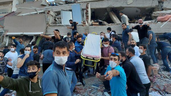 Ratownicy i mieszkańcy ewakuują ofiary podczas zawalenia się budynku w wyniku trzęsienia ziemi, Izmir, Turcja - Sputnik Polska