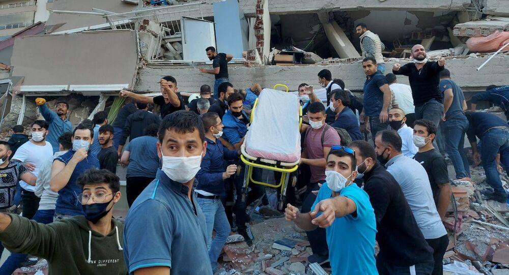 Ratownicy i mieszkańcy ewakuują ofiary podczas zawalenia się budynku w wyniku trzęsienia ziemi, Izmir, Turcja.