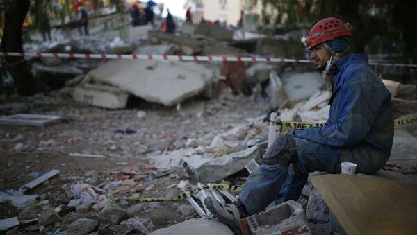 Ratownik odpoczywający na miejscu zniszczonego budynku po trzęsieniu ziemi w Izmirze - Sputnik Polska