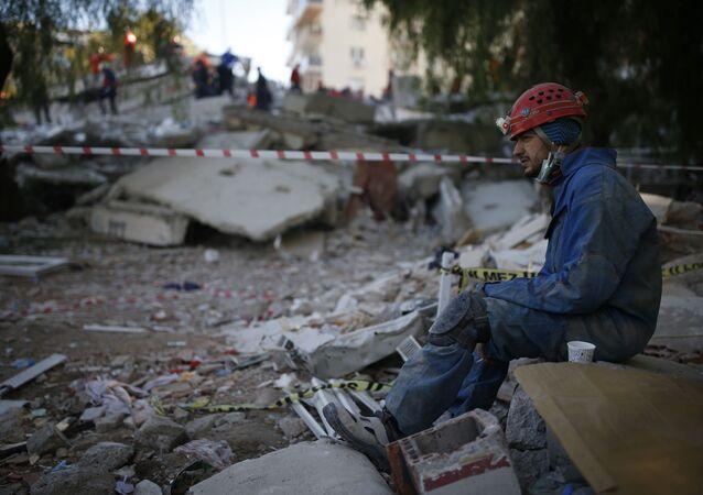 Ratownik odpoczywający na miejscu zniszczonego budynku po trzęsieniu ziemi w Izmirze