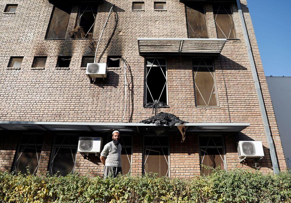 Mężczyzna przed budynkiem uniwersytetu w Kabulu, który został zaatakowany