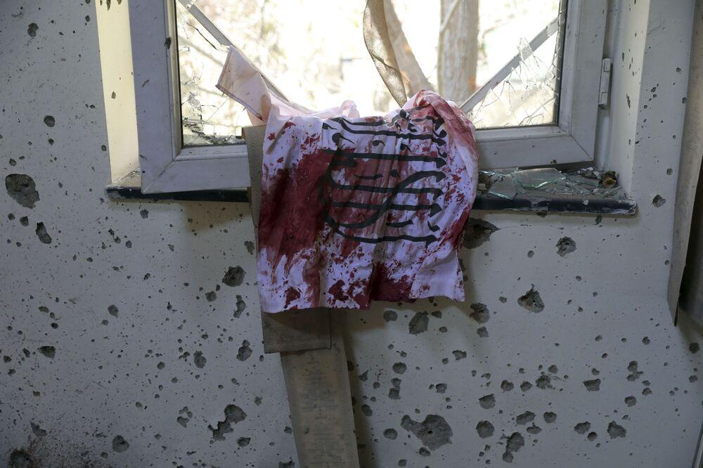 Krwawa flaga talibów na oknie uniwersytetu w Kabulu, który został zaatakowany