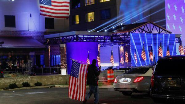 Zwolennik Bidena trzymający flagę w dniu wyborów prezydenckich w Delaware w USA - Sputnik Polska