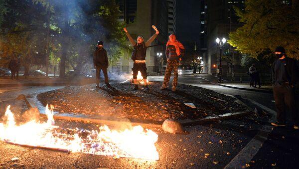 Protestujący palą amerykańską flagę przed budynkiem sądu w Portland w stanie Oregon w USA - Sputnik Polska