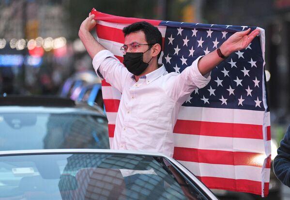 Mężczyzna z flagą USA na Times Square w Nowym Jorku po wiadomościach o zwycięstwie kandydata Demokratów Joe Bidena w wyborach prezydenckich w USA - Sputnik Polska