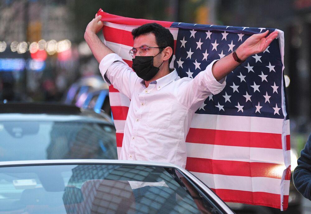 Mężczyzna z flagą USA na Times Square w Nowym Jorku po wiadomościach o zwycięstwie kandydata Demokratów Joe Bidena w wyborach prezydenckich w USA
