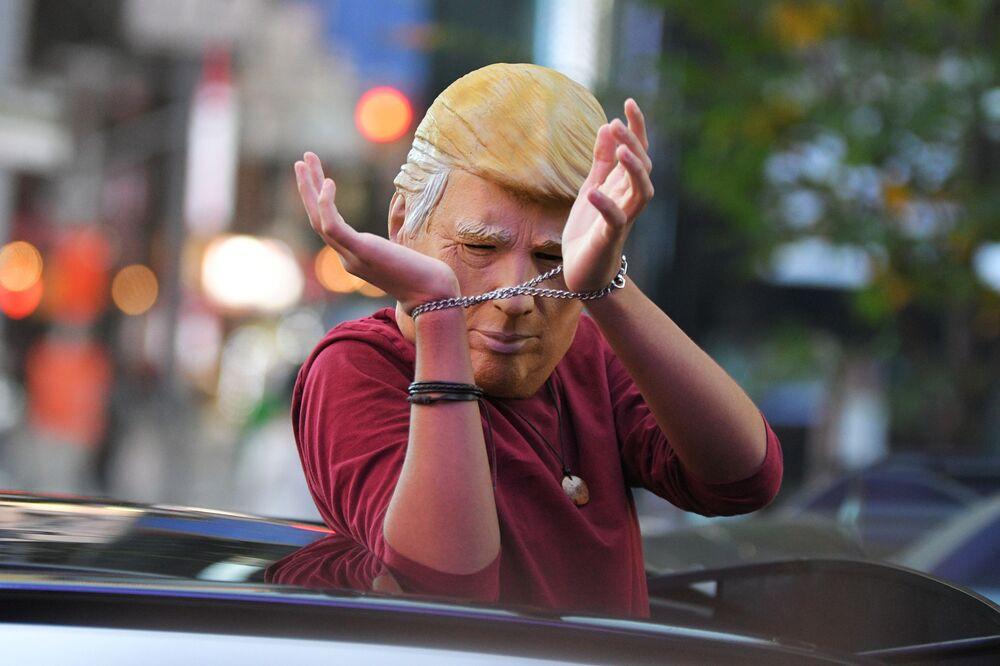 Mężczyzna w masce Donalda Trumpa jedzie ulicą Nowego Jorku po wiadomościach o zwycięstwie Joe Bidena w wyborach prezydenckich w USA