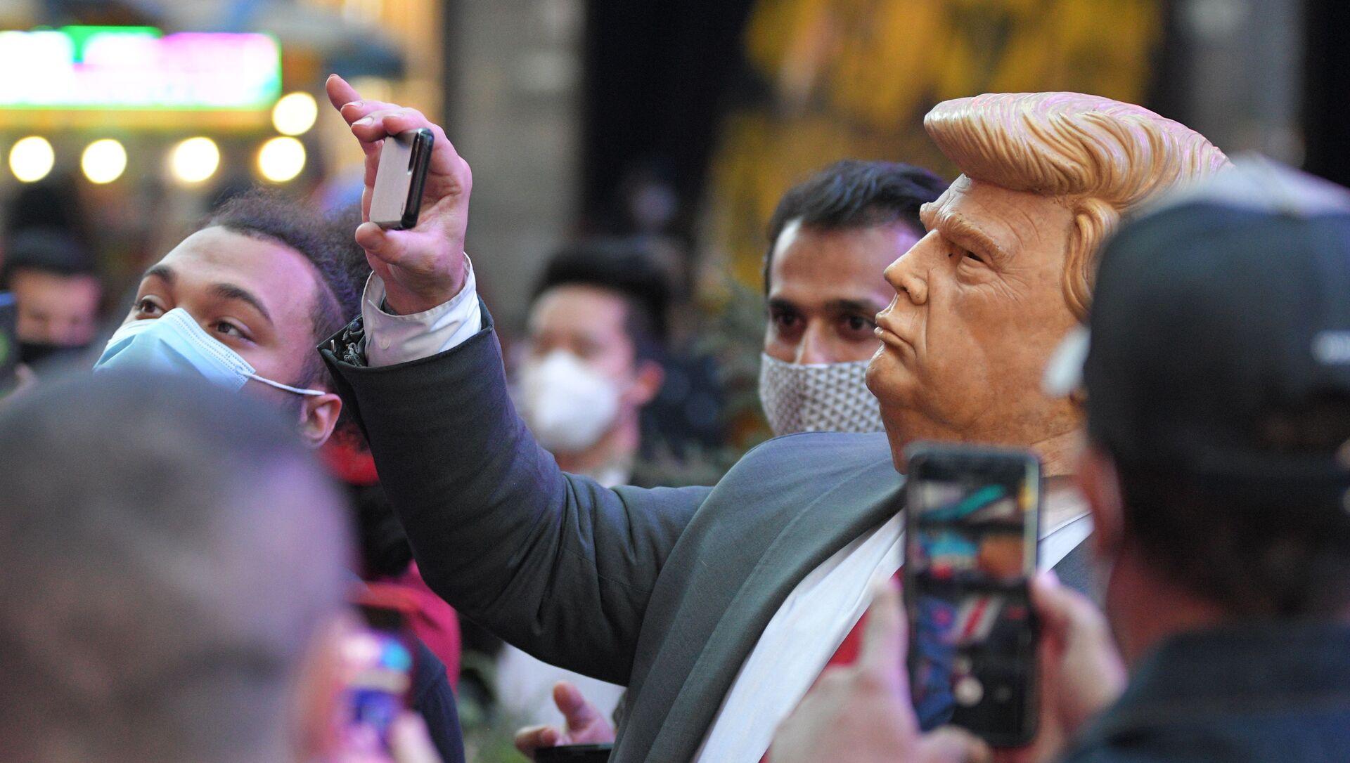 Ludzie na Times Square w Nowym Jorku fotografują mężczyznę w masce Donalda Trumpa - Sputnik Polska, 1920, 16.02.2021