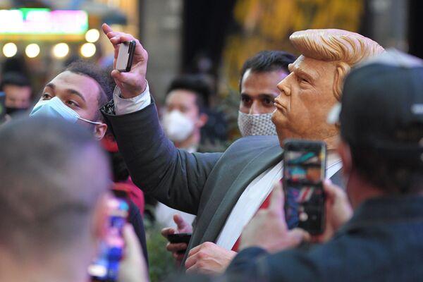 Ludzie na Times Square w Nowym Jorku fotografują mężczyznę w masce Donalda Trumpa - Sputnik Polska