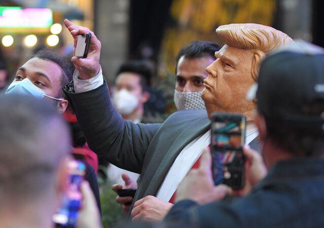 Ludzie na Times Square w Nowym Jorku fotografują mężczyznę w masce Donalda Trumpa