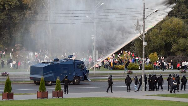 Policyjny samochód polewa wodą protestujących w Mińsku - Sputnik Polska