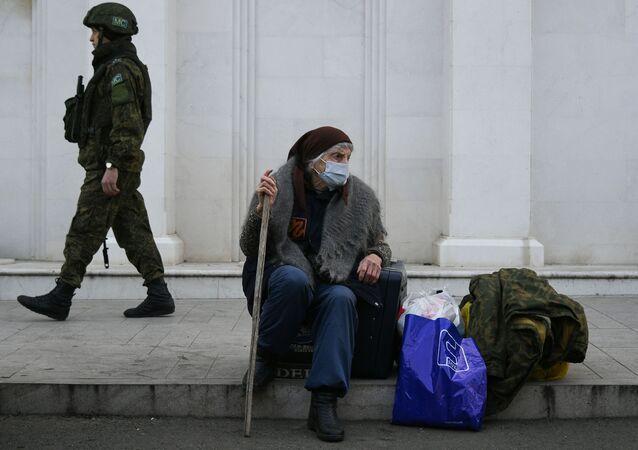 Rosyjski żołnierz sił pokojowych i starsza kobieta na ulicy Stepanakertu