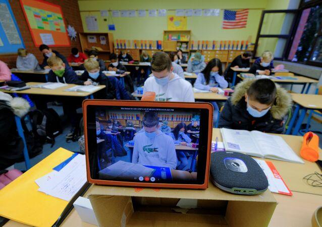 Uczniowie biorą udział w wirtualnej lekcji angielskiego prowadzonej przez nauczyciela poddanego kwarantannie domowej w Niemczech.