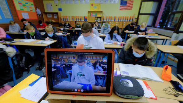 Uczniowie biorą udział w wirtualnej lekcji angielskiego prowadzonej przez nauczyciela poddanego kwarantannie domowej w Niemczech. - Sputnik Polska