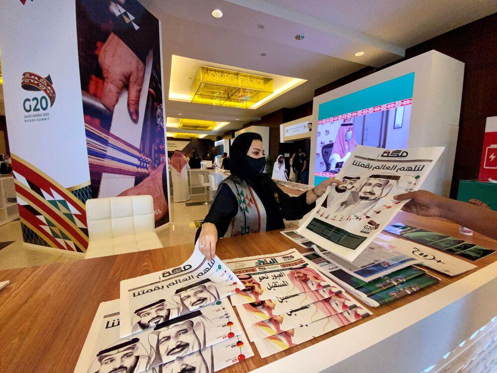Personel centrum medialnego rozdaje gazety przed 15. dorocznym szczytem przywódców G20 w Rijadzie w Arabii Saudyjskiej