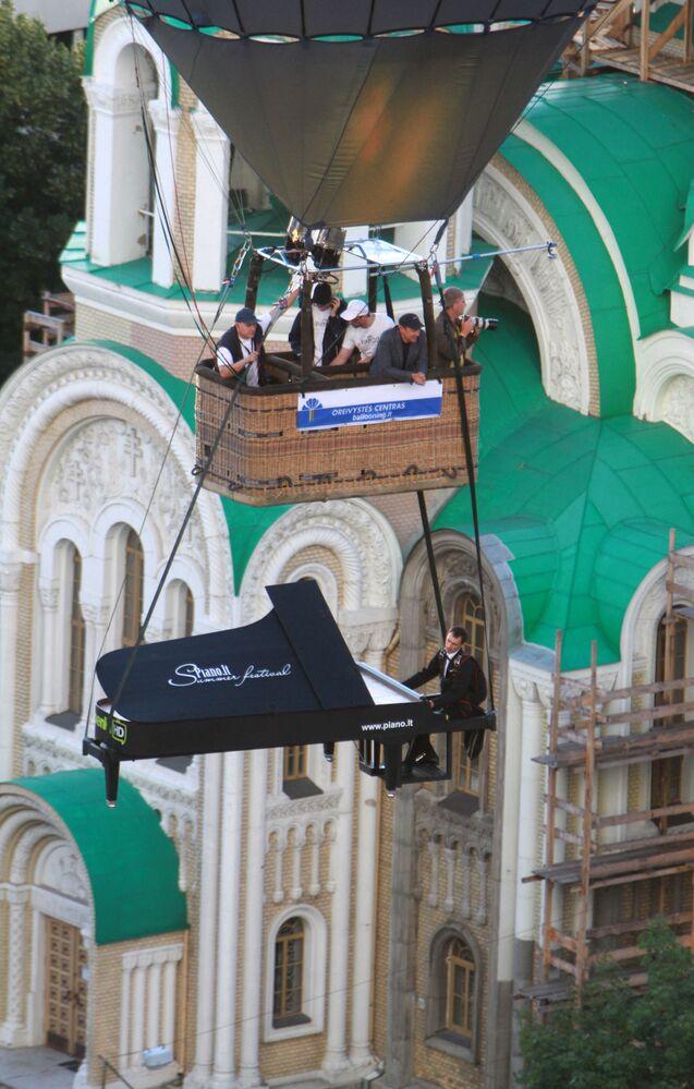 """Kaskader """"gra"""" na pianinie z kartonu podczas festiwalu balonów w Wilno"""