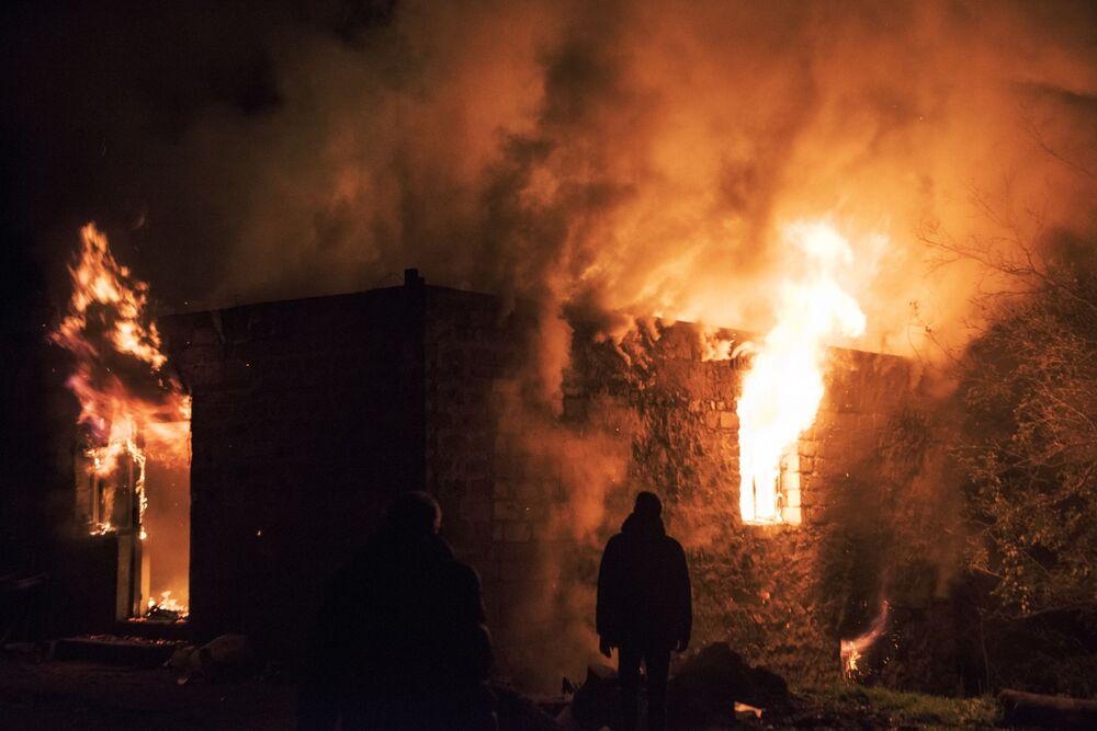 Mieszkańcy wsi Karegach w pobliżu płonącego domu.