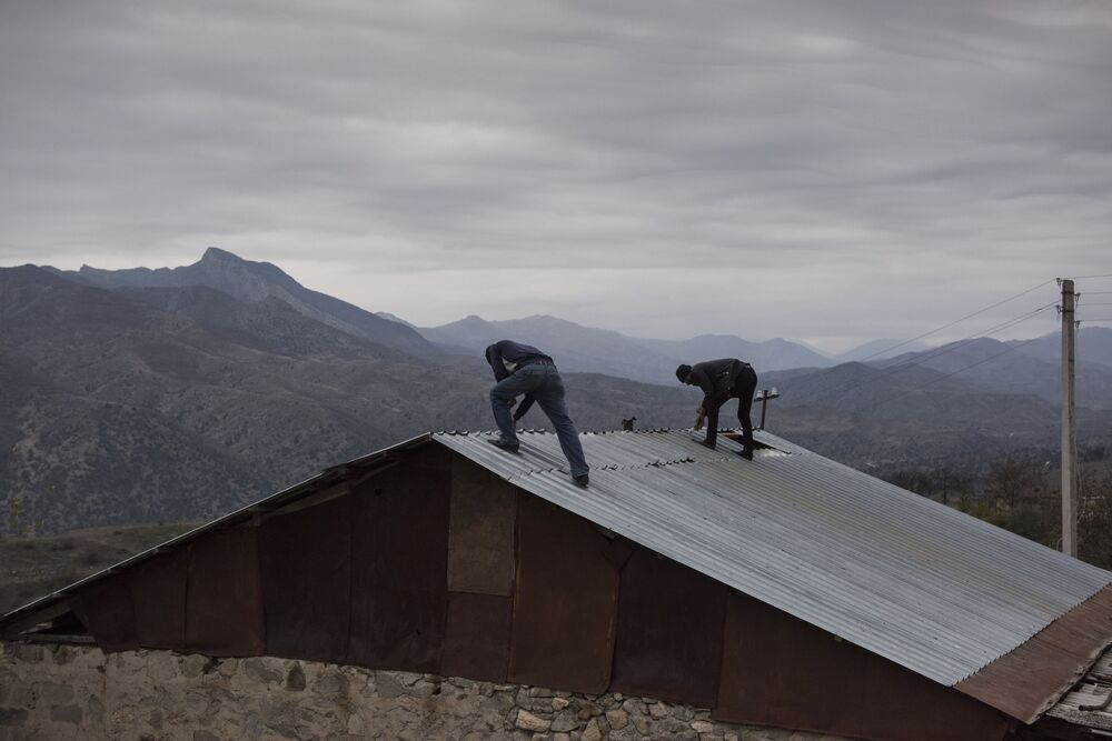 Mężczyźni demontują dach domu we wsi Karegach.