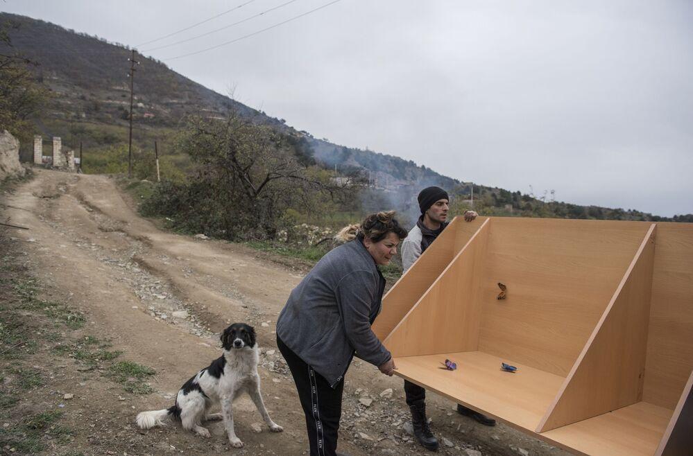 Mieszkańcy Karegachu ładują meble do samochodu przed opuszczeniem wioski.
