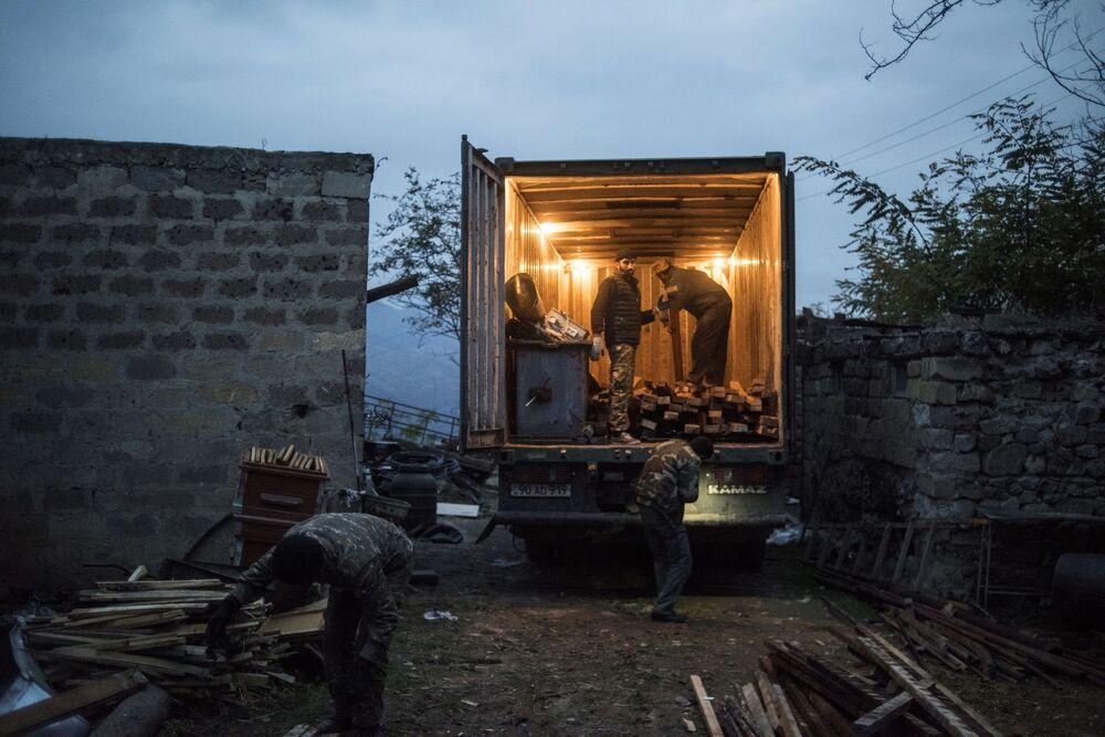 Mieszkańcy wioski Karegach ładują rzeczy osobiste do ciężarówki.