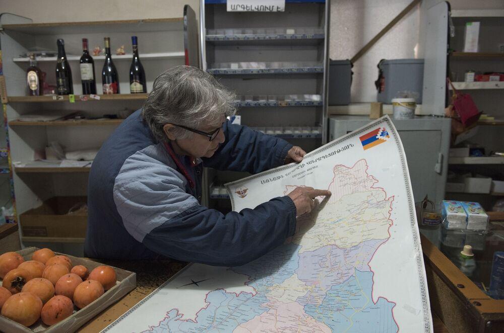 Mężczyzna pokazuje mapę w sklepie w Lachin.