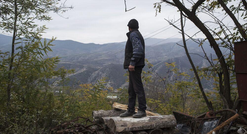 Mieszkaniec wsi Karegach patrzy na góry przed swoim domem.