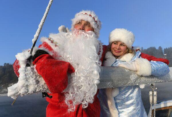 """Członkowie klubu jachtowego """"Skiper"""" w kostiumach Dziadka Mroza i Śnieguroczki biorą udział w ostatnim w 2020 wyjściu jachtu żaglowego """"Wiktor"""" na wody Jeniseju - Sputnik Polska"""