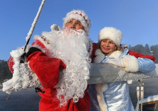 """Członkowie klubu jachtowego """"Skiper"""" w kostiumach Dziadka Mroza i Śnieguroczki biorą udział w ostatnim w 2020 wyjściu jachtu żaglowego """"Wiktor"""" na wody Jeniseju."""