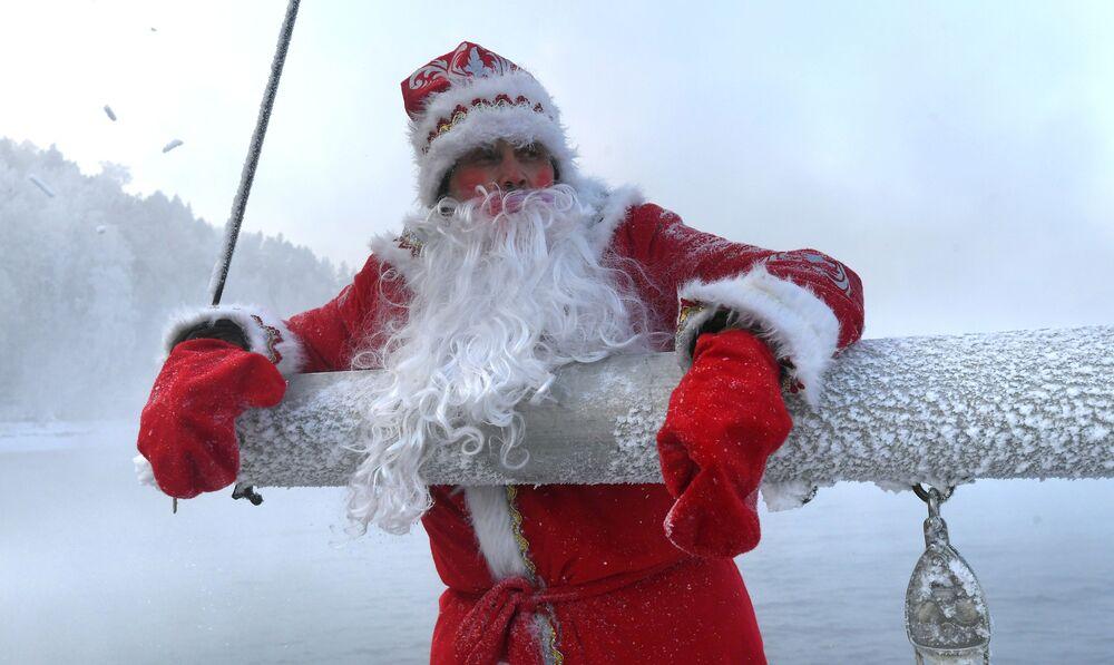 """Członek klubu jachtowego """"Skiper"""" w przebraniu Dziadka Mroza bierze udział w ostatnim w 2020 roku wyjściu jachtu żaglowego """"Wiktor"""" na wody Jeniseju."""