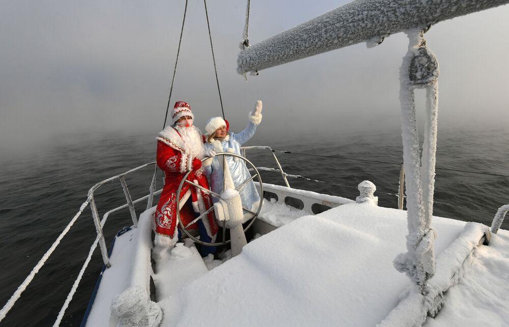 """Członkowie klubu jachtowego w przebraniach Dziadka Mroza i Świętego Mikołaja biorą udział w ostatnim w 2020 roku wyjściu jachtu żaglowego """"Wiktor"""" na wody Jeniseju."""