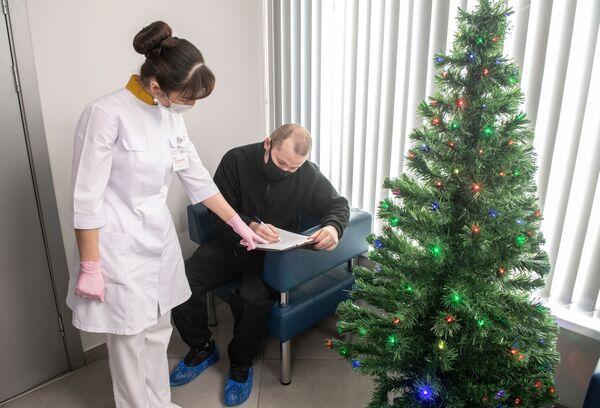 Lekarz i pacjent w ośrodku szczepień przeciwko COVID-19 miejskiej przychodni w Moskwie - Sputnik Polska