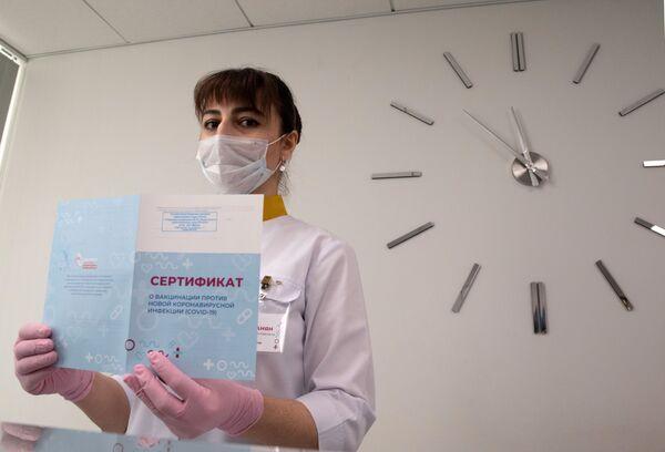 """Lekarz demonstruje """"Świadectwo szczepień przeciwko nowej infekcji koronawirusem COVID-19"""" w Moskwie - Sputnik Polska"""