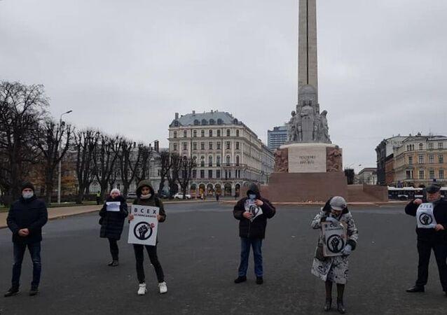 Ludzie trzymają plakaty na wiecu poparcia dla dziennikarzy w Rydze, Łotwa