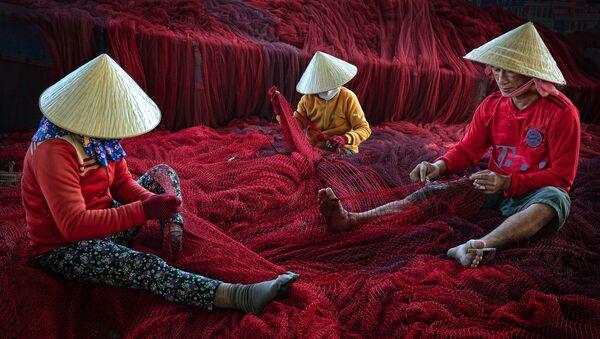 To zdjęcie przedstawia rybaków i członków ich rodzin naprawiających sieć przed kolejną wycieczką łodzią w prowincji Ninh Thuan na południowo-środkowym wybrzeżu Wietnamu. Hoang Long od 1999 roku zdobył ponad 200 krajowych i międzynarodowych nagród, w tym wygrał kategorię regionu Azji i Pacyfiku w konkursie CBRE Urban Photographer of the Year 2014 - Sputnik Polska