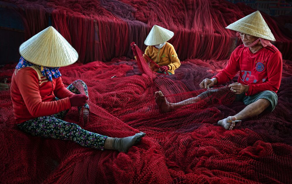 To zdjęcie przedstawia rybaków i członków ich rodzin naprawiających sieć przed kolejną wycieczką łodzią w prowincji Ninh Thuan na południowo-środkowym wybrzeżu Wietnamu. Hoang Long od 1999 roku zdobył ponad 200 krajowych i międzynarodowych nagród, w tym wygrał kategorię regionu Azji i Pacyfiku w konkursie CBRE Urban Photographer of the Year 2014