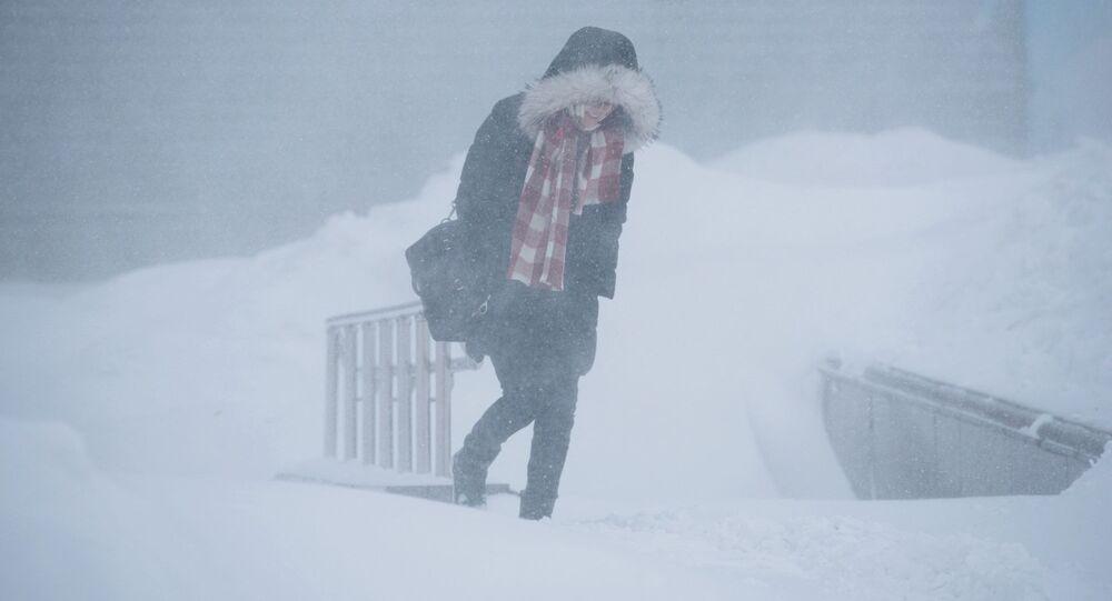 Dziewczyna idzie ulicą podczas burzy śnieżnej