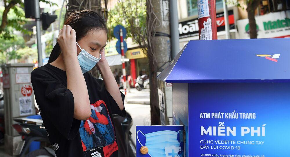 Dziewczyna w masce medycznej przy automacie z darmowymi maskami w Hanoi.