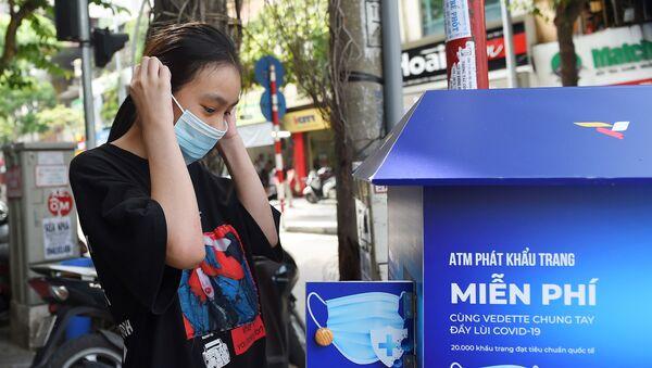 Dziewczyna w masce medycznej przy automacie z darmowymi maskami w Hanoi - Sputnik Polska