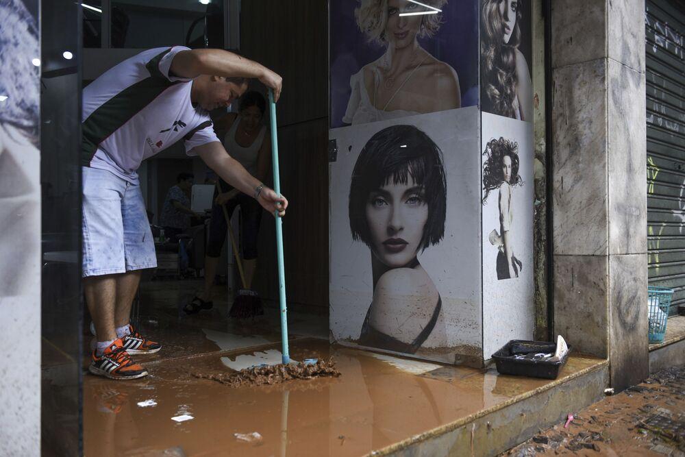 Mężczyzna usuwa brud ze sklepu po powodzi w brazylijskim Belo Horizonte