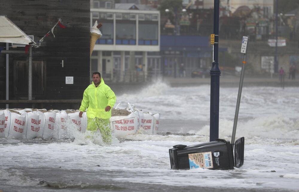 Mężczyzna na zalanym nabrzeżu Swanage w Wielkiej Brytanii