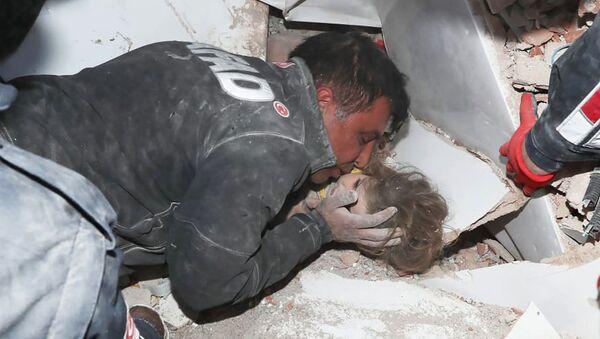 Tureccy ratownicy wyciągają dziecko z gruzów po trzęsieniu ziemi w Izmirze - Sputnik Polska