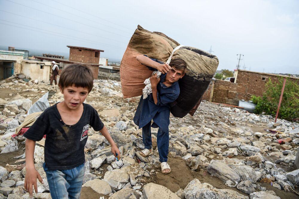 Młodzi ludzie ratują pozostałości dobytku z ruin domów po powodzi w Charikar w prowincji Parwan w Afganistanie