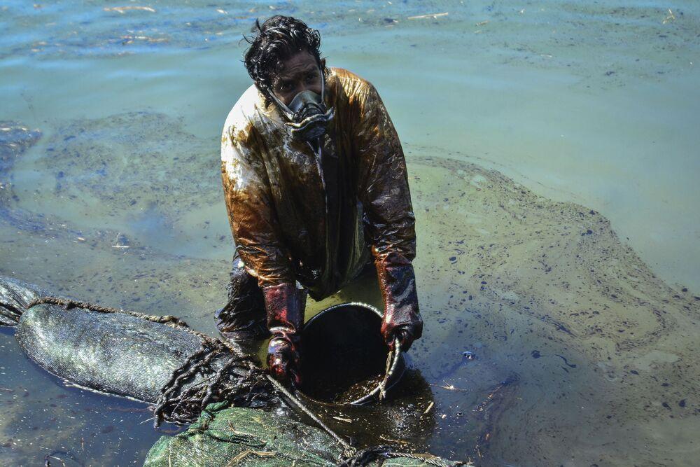 Mężczyzna oczyszcza wodę z wycieków ropy u wybrzeży Mauritiusa